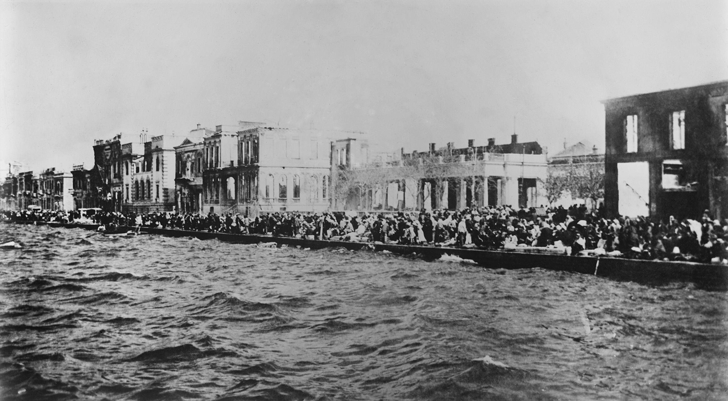 Thousands of Greek and Armenian refugees crowd onto Smyrna's waterfront to escape the fire of September 1922.