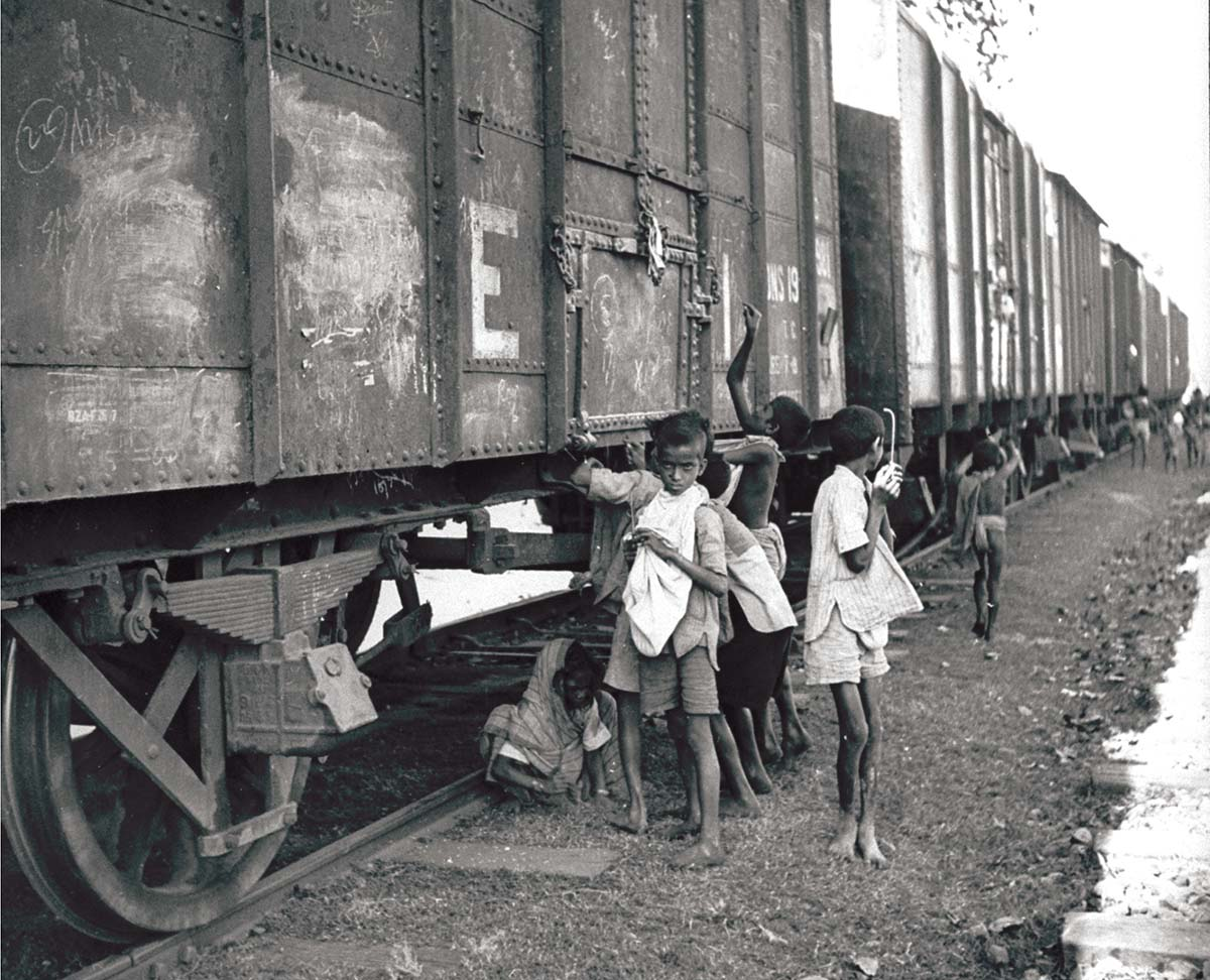 Children trying to pierce bags of grain in stationary train carriages, Bengal, 1943 © William Vandivert/LIFE/Getty Images