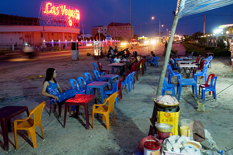 People at tables eating street food in the casino area of Bavet, Cambodia.