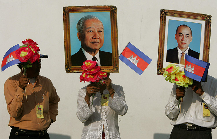 Cambodians hold portraits of King Norodom Sihamoni (right) and his father, King Norodom Sihanouk (left), October 20th, 2004.