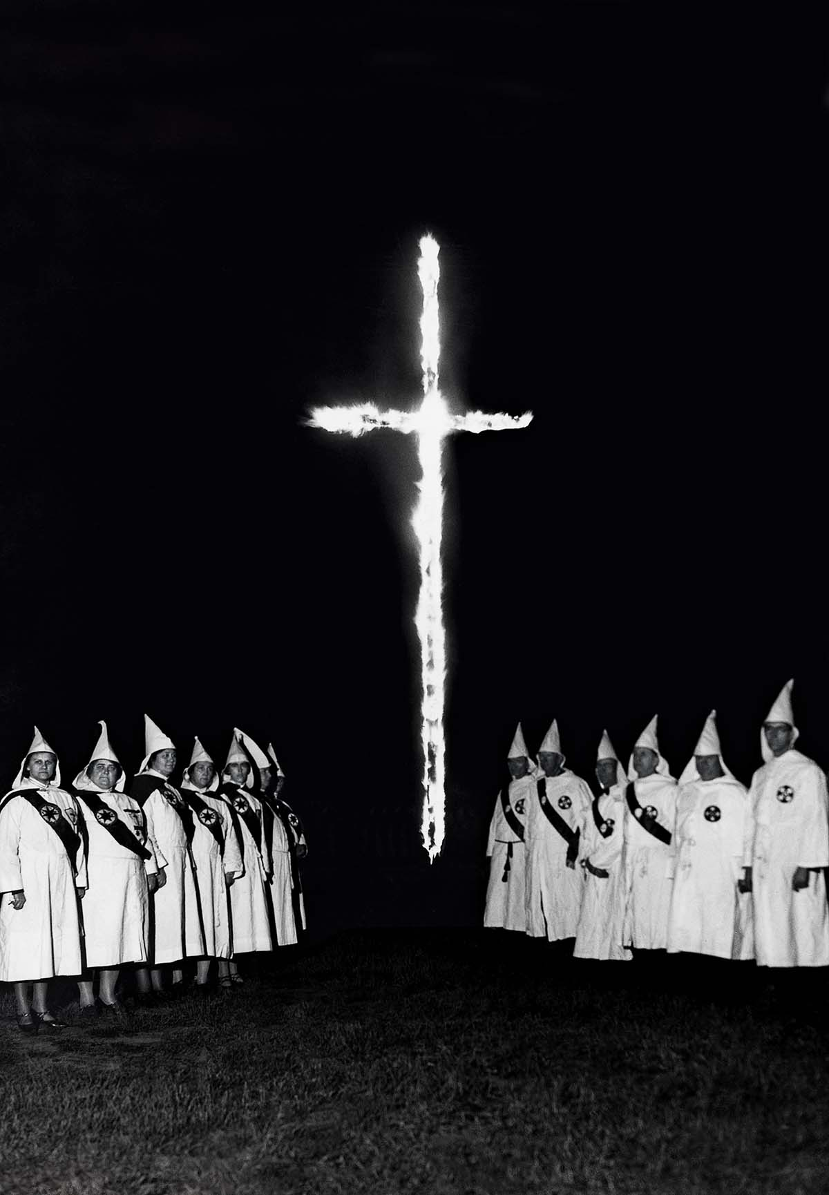 Klansmen and woman surround a burning cross, c.1940s. Getty Images.