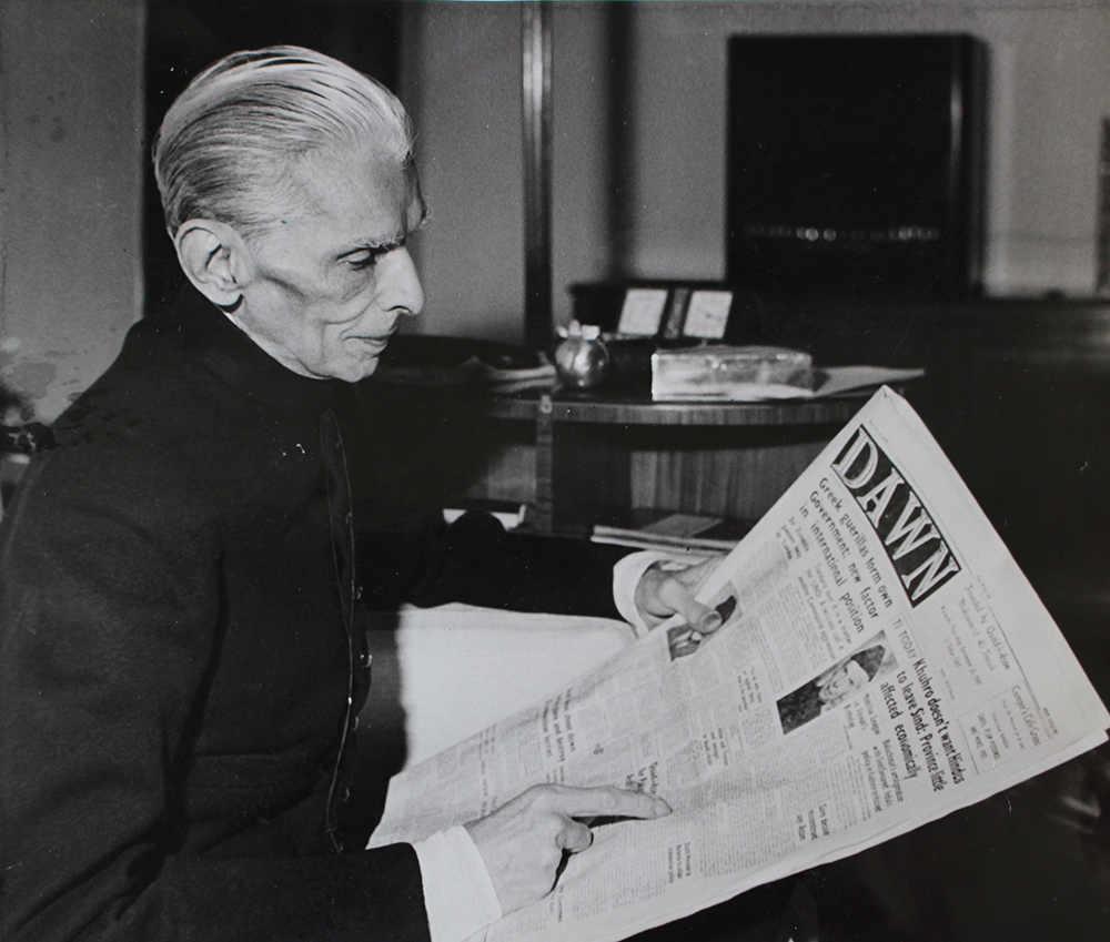 Jinnah reads a copy of the Pakistani newspaper Dawn, published to mark his 71st birthday, 25 December 1947.