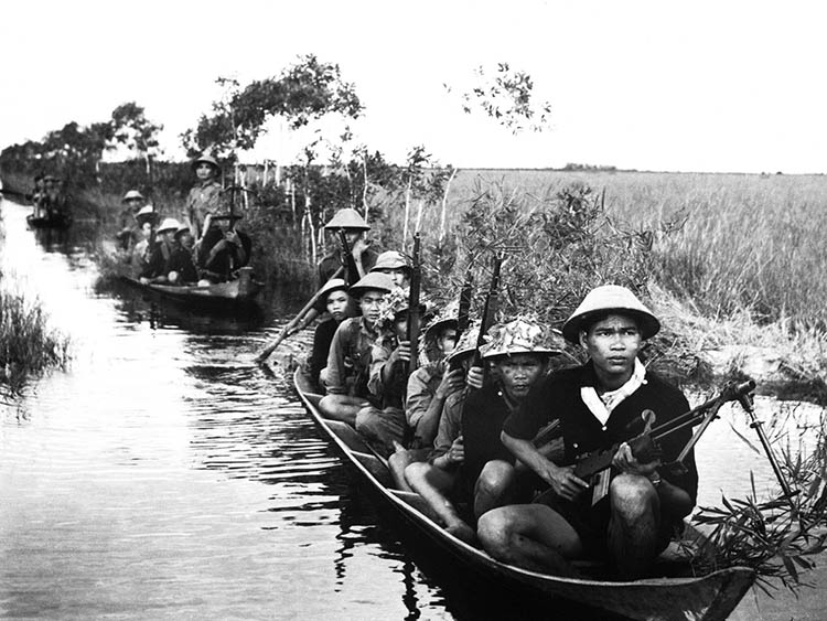 Guerrilla forces from North Vietnam's Viet Cong move across a river in 1966.