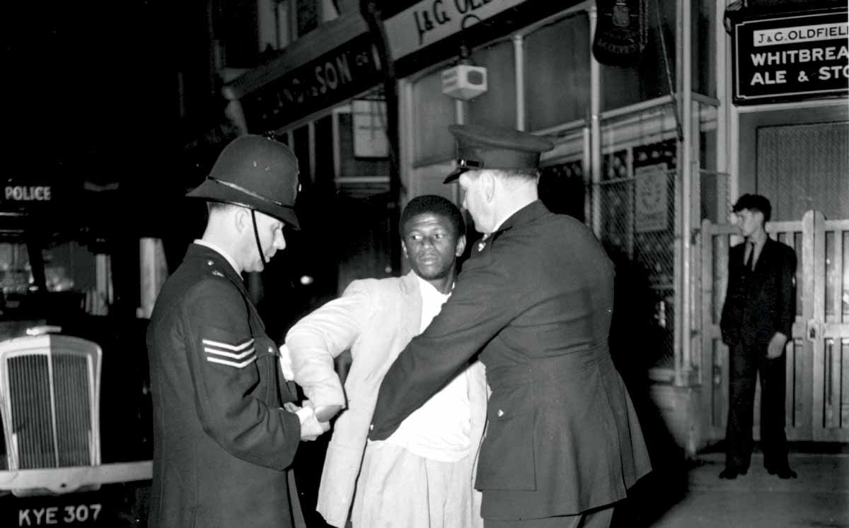 London police search a black youth on Talbot Road, Notting Hill, during the race riots, 3 September 1958 © Getty Images.