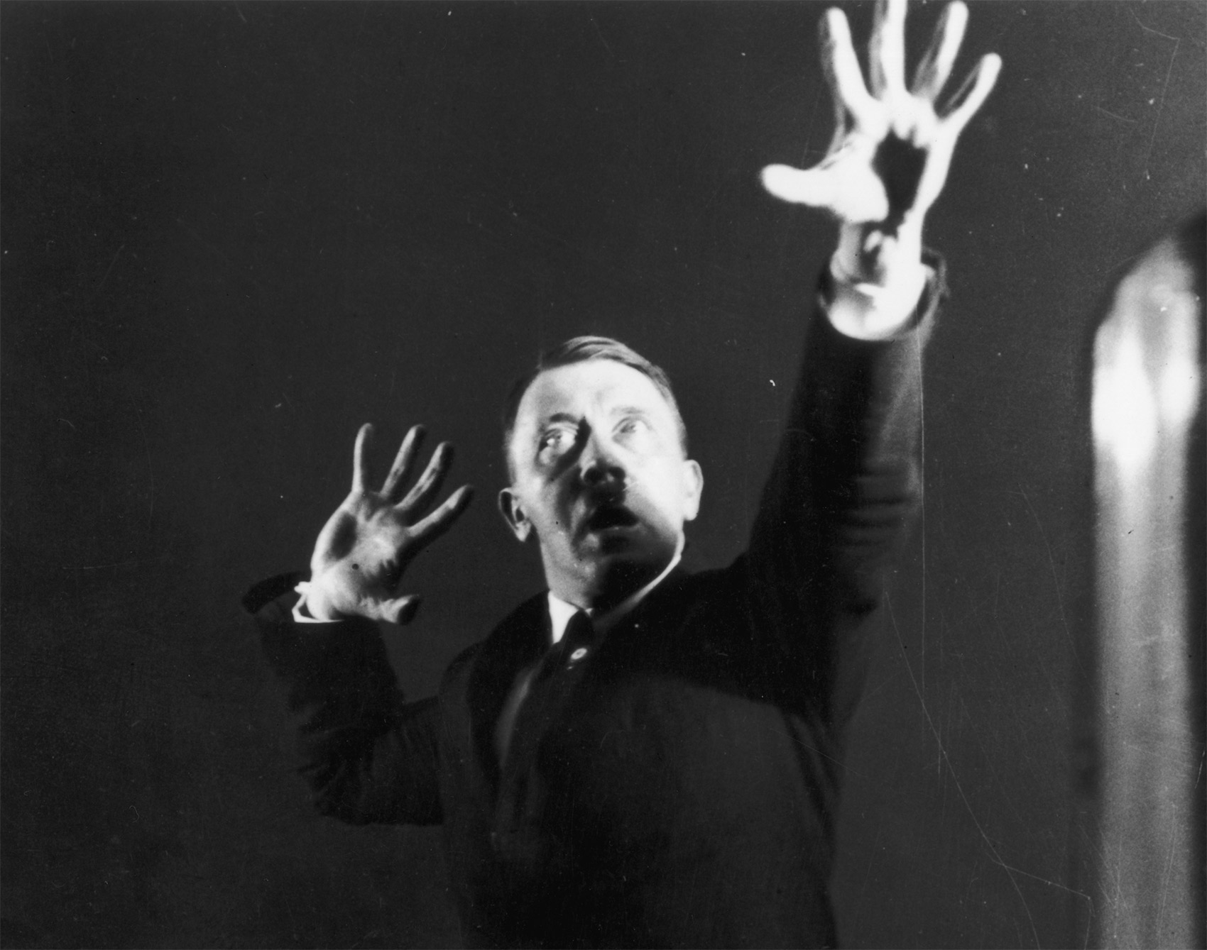 Hitler miming gestures to a record of his speeches; part of a series of photographs he commissioned in 1925 to aid self-analysis and improve his hold over an audience.