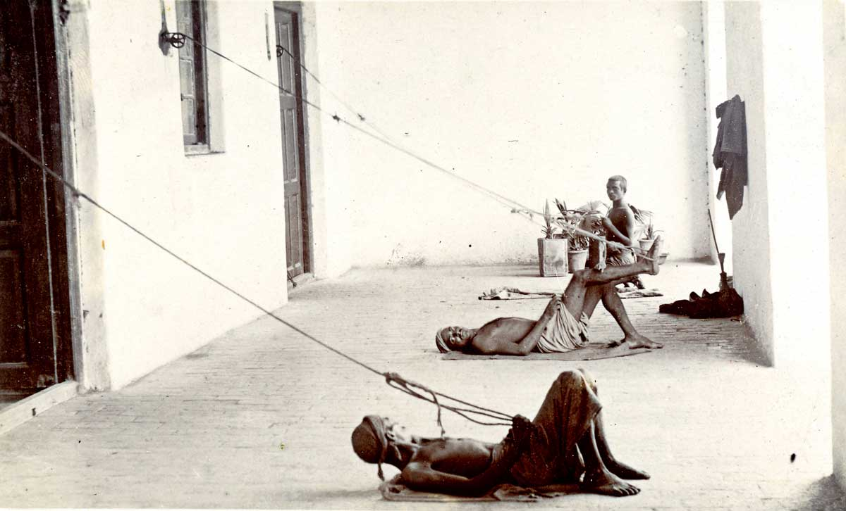 Three Indian men on a verandah pulling punkha strings, c.1900 © Royal Society for Asian Affairs, London/Bridgeman Images