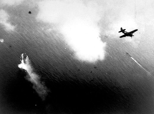 U.S. aircraft, such as this Curtiss SB2C-3 Helldiver, begin their attacks on Yamato (center left). A Japanese destroyer is in the center right of the picture.