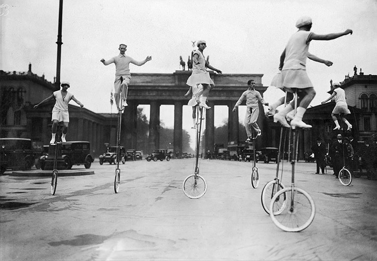 Unicyclists on Pariser Platz in front of the Brandenburg Gate, Berlin, c.1920.