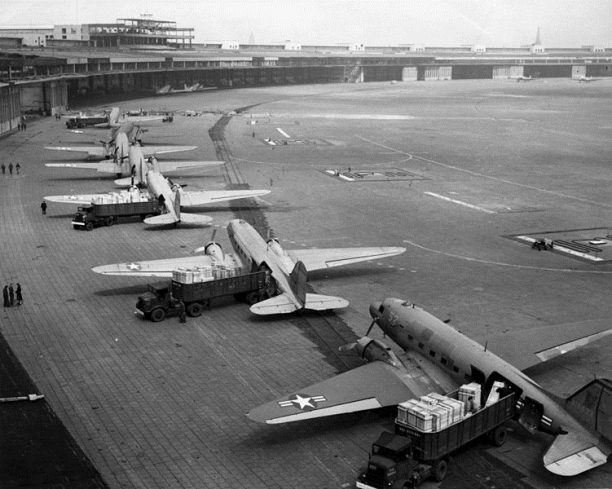 U.S. Navy Douglas R4D and U.S. Air Force C-47 aircraft unload at Tempelhof Airport during the Berlin Airlift, 1948-49