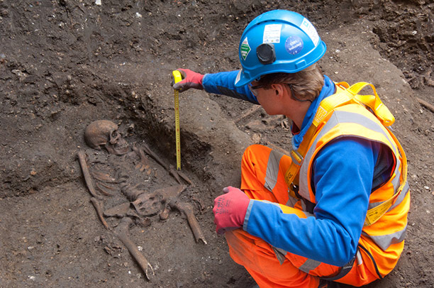 An archaeologist measures one of the skeletons. Photograph courtesy of Crossrail