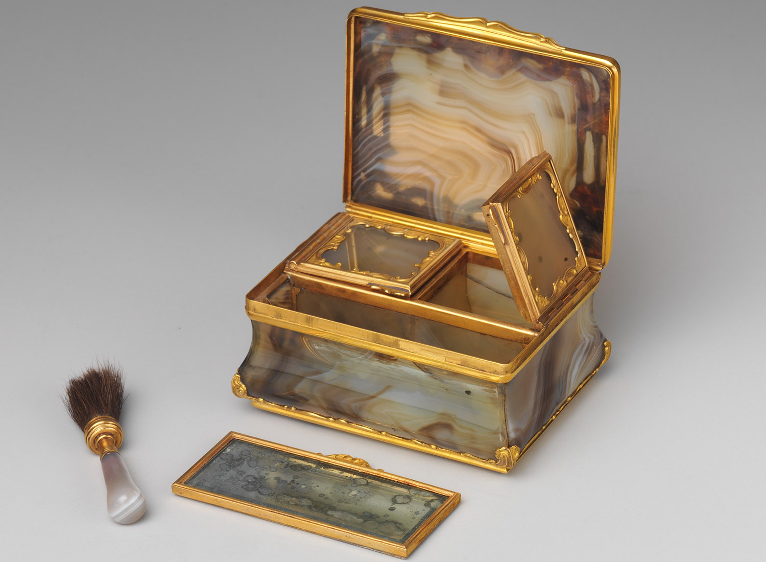 Resembling a snuffbox but smaller in size, this boîte à mouches contains two closed compartments—one to hold rouge and the other for black taffeta patches. A tiny brush and mirror were placed in the larger compartment.
