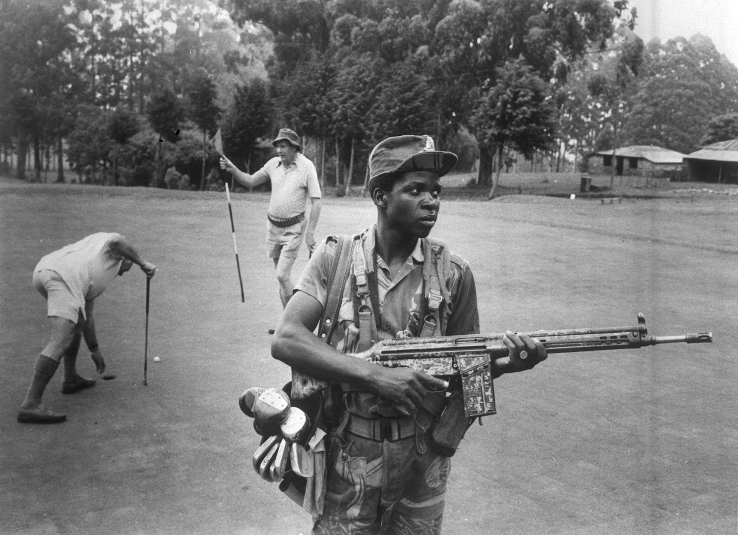 An armed guard provides security for white Rhodesian golfers at the Leopard Rock Hotel, Manicaland, 1978. Eddie Adams / Press Association Images