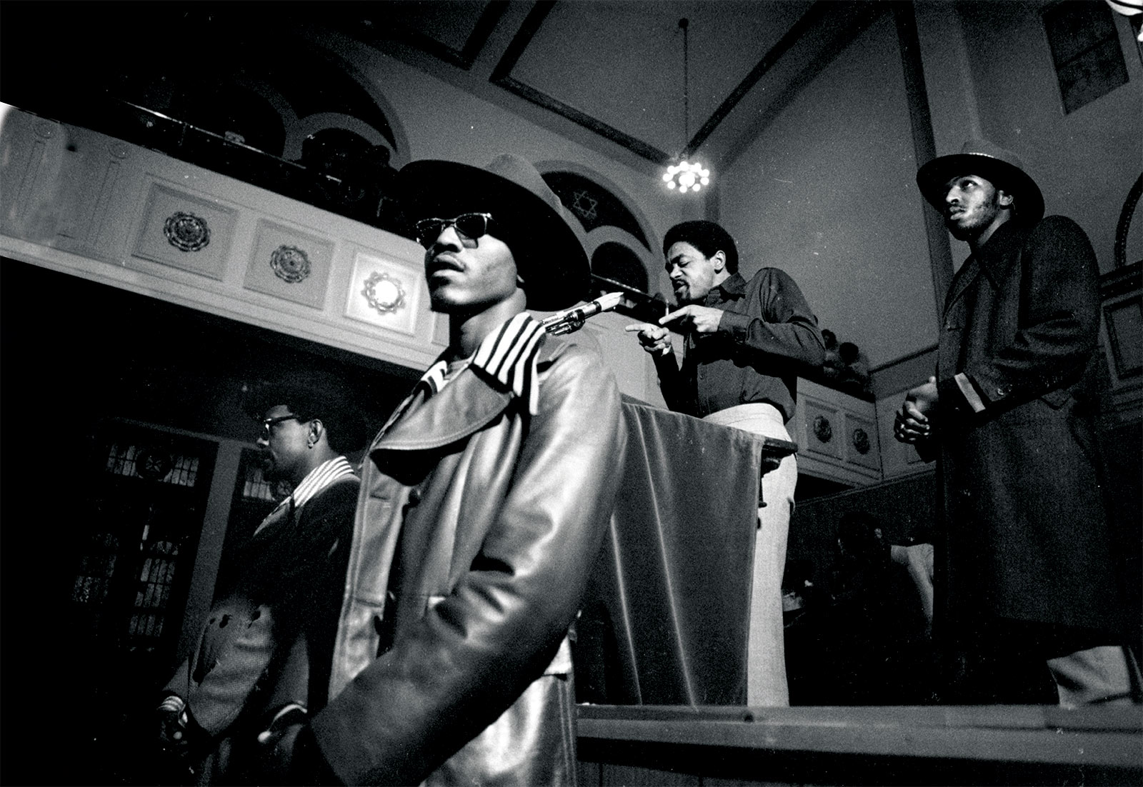 Black Panther Party leader Bobby Seale addresses a crowd from the podium flanked by bodyguards, Chicago, 1971.