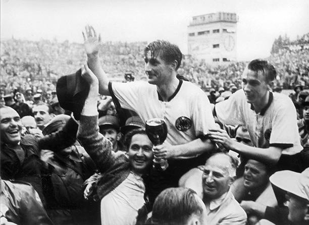 Captain Fritz Walter (with the Jules Rimet trophy) and midfielder Horst Eckel are carried aloft by supporters. Corbis/DPA