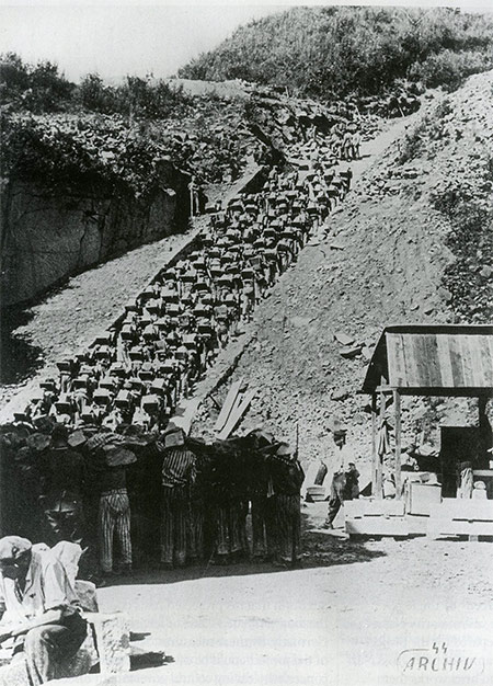 Prisoners at Mauthausen concentration camp are forced to carry granite blocks up the stone 'stairs of death', c. 1943