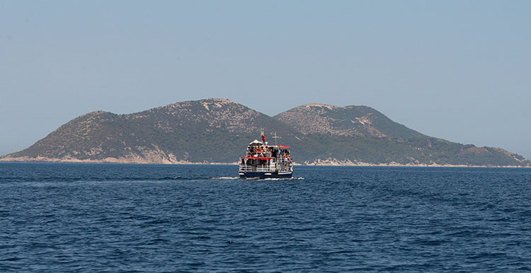 A tourist boat heads to the former military island of Sazan, July 2015.