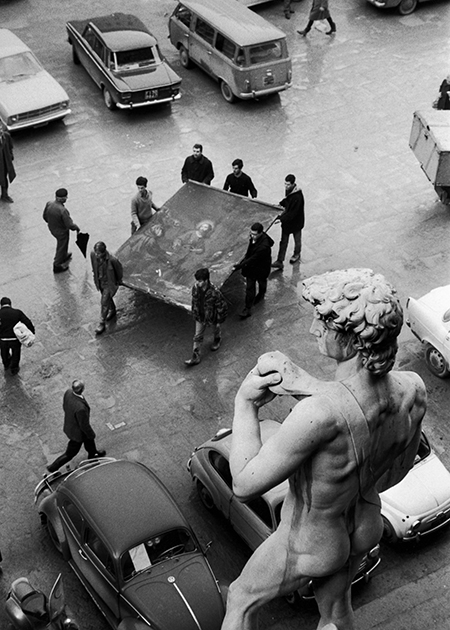 A monumental task: volunteers carry a painting to safety past the replica David in the Piazza della Signoria, 1966.