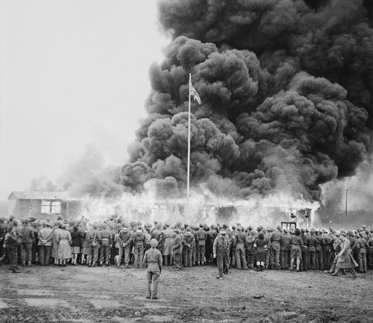 A crowd watches the destruction of the last camp hut.