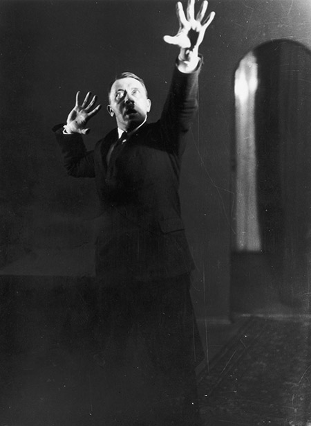 Hitler miming gestures to a record of his speeches; one of an extraordinary series of photographs he commissioned in 1925 to aid self-analysis and improve his hold over an audience.