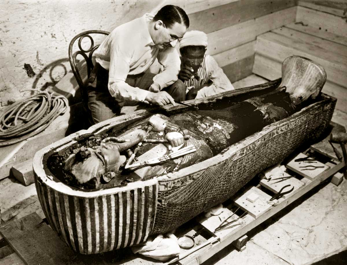 Howard Carter inspects the golden sarcophagus of Tutankhamun, Egypt, 1922.
