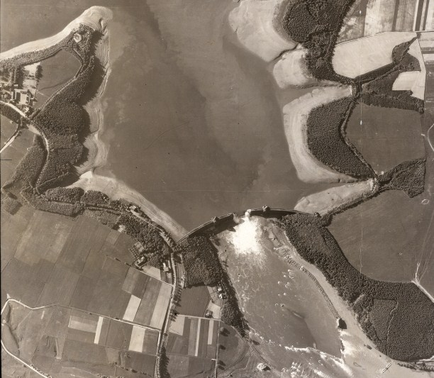 One of the most famous aerial photographs of the Second World War was taken from 30,000 feet on May 17th, 1943, only hours after the Dam Busters raid. The water from the reservoir is stil gushing through the 200-foot breech in the Mohne Dam. Mudflats appear as the water level drops above the dam. Photo / Trustees of the Medmenham Collection