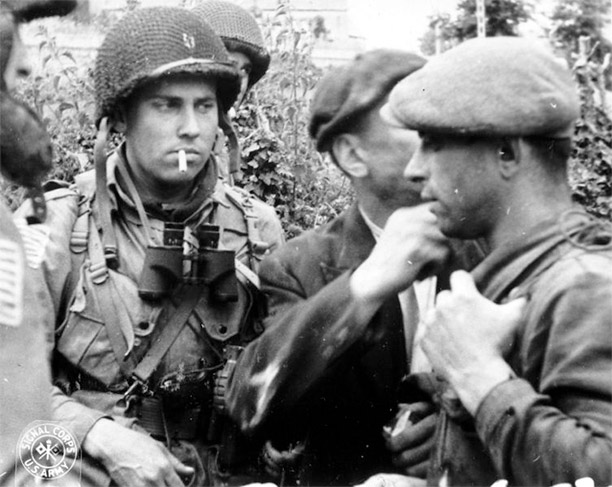 French Resistance members and Allied paratroopers discuss the situation during the Battle of Normandy in 1944