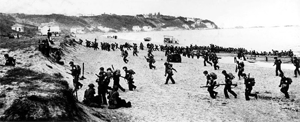Allied troops hit the beaches near Algiers, behind a large American flag (left).
