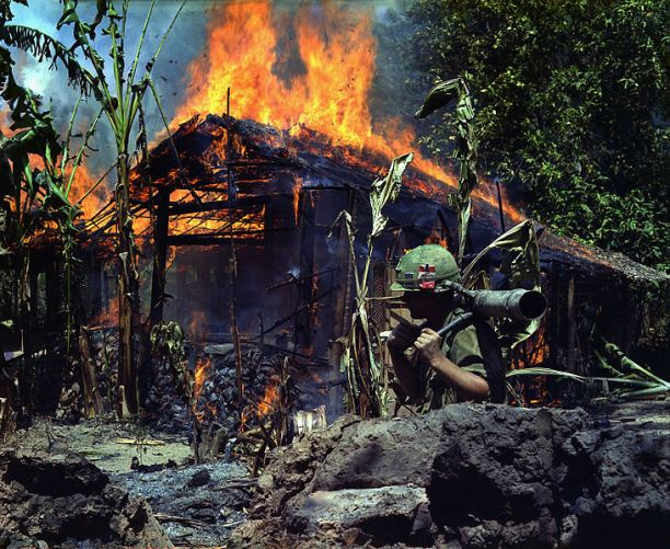 U.S. soldier carries a M67 recoilless rifle past a burning Viet Cong base camp in My Tho, South Vietnam, 1968