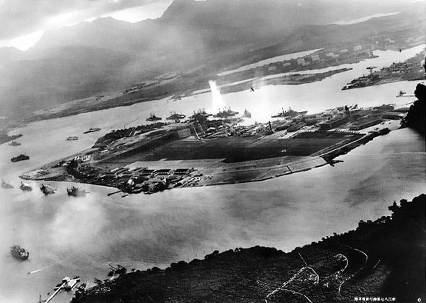 Photograph from a Japanese plane of Battleship Row at the beginning of the attack. The explosion in the center is a torpedo strike on the USS Oklahoma. Two attacking Japanese planes can be seen: one over the USS Neosho and one over the Naval Yard.