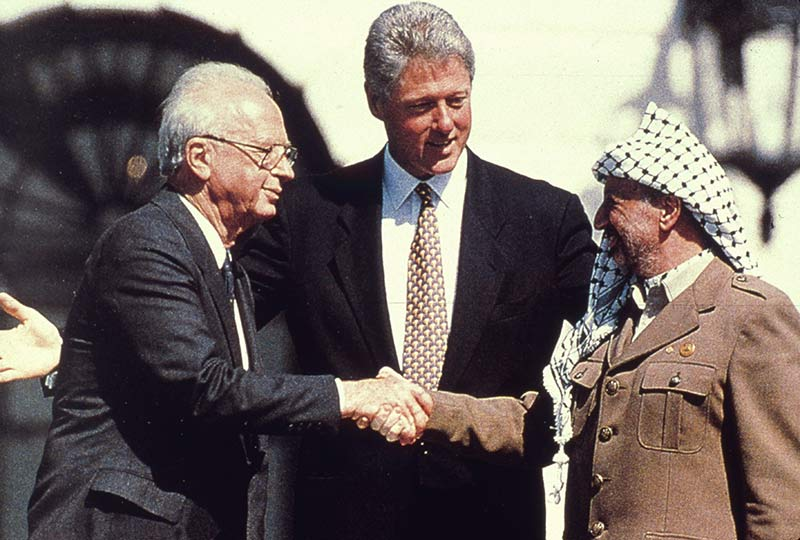 President Bill Clinton watches Yitzhak Rabin and Yasser Arafat shake hands in the garden of the White House, 13 September 1993.