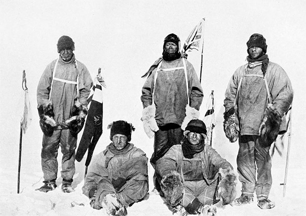 Photograph of the party taken January 17th, 1912, the day after they discovered Amundsen had reached the South Pole first. Left to right: Oates (standing), Bowers (sitting), Scott (standing in front of Union Jack flag on pole), Wilson (sitting), Evans (standing). Bowers took this photograph, using a piece of string to operate the camera shutter.