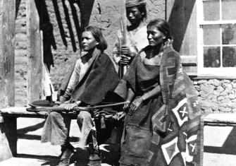 A Navajo woman and  two young men at Ford Defiance, in what was then New Mexico, 1873.