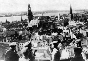 German soldiers look out over Riga's old town from the tower of St Peter's Church, 1917 © Bridgeman Images