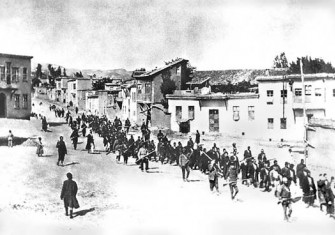 Armenian civilians, escorted by armed Ottoman soldiers, are marched through Harput (Kharpert), April 1915.
