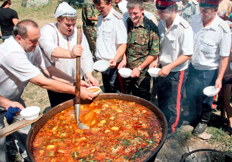 Don Cossacks in army uniform wait in line for borscht, 2006.