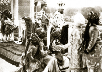 George V and Queen Mary watching the Delhi Durbar from the Red  Fort, accompanied by Indian princes acting as pages, 1911.