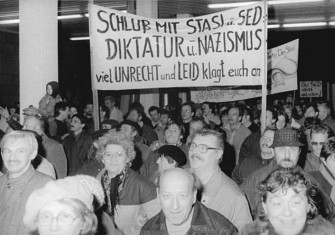 Citizens protesting and entering the Stasi building in Berlin; the sign accuses the Stasi and SED of being Nazi-like dictators.