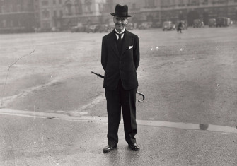 Neville Chamberlain stands, with his umbrella, on Horse Guards Parade, off Whitehall, London, 18 March 1940.