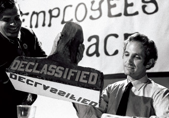 Daniel Ellsberg being presented with a papier-mâché 'Declassified' stamp on 23 September 1971, at a banquet held by the Federal Employees for Peace.