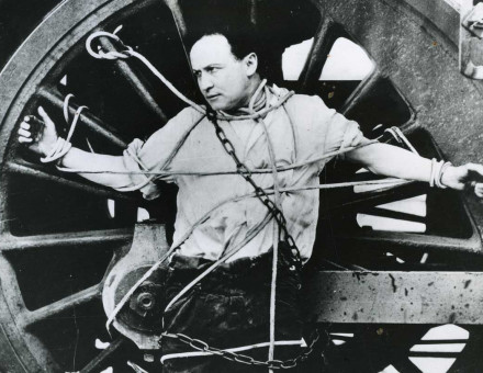 Harry Houdini strapped to a locomotive wheel, c.1910.