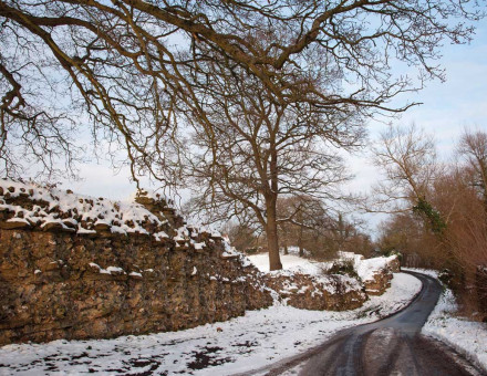 A road runs past the remains of the Roman wall at Silchester.