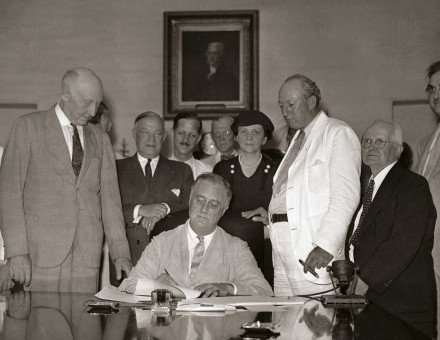 President Roosevelt signs the Social Security Act in the White House, 1935. Harrison is in the white suit.