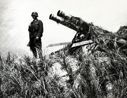 Quiet posting: a soldier in German uniform stands with a captured Dutch gun at Texel, May, 1940.