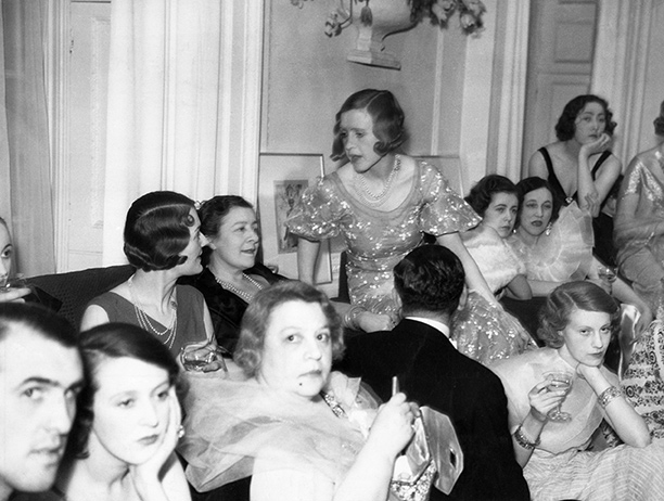 A fashionable crowd surround Syrie (wearing a dark dress and seated on the sofa) at a party given by the couturier Victor Stiebel at his Mayfair home, 1933. Getty Images/Hulton Archive