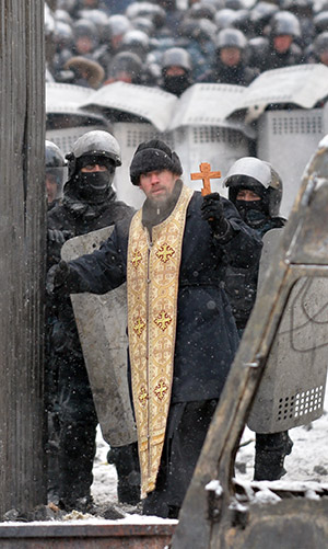 Man of peace: an Orthodox priest comes between police and protestors in Kiev, January 22nd, 2014. Getty/AFP/Sergei Supinsky