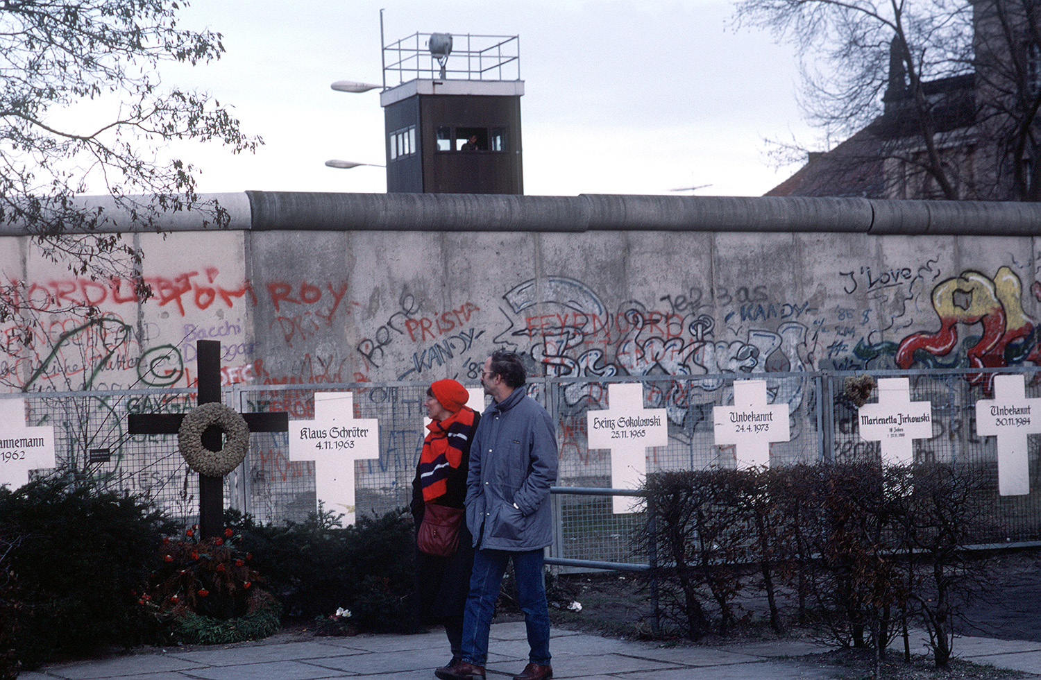 A couple reads grave markers of East Germans who died trying to escape East Germany across the Berlin Wall, 1990.
